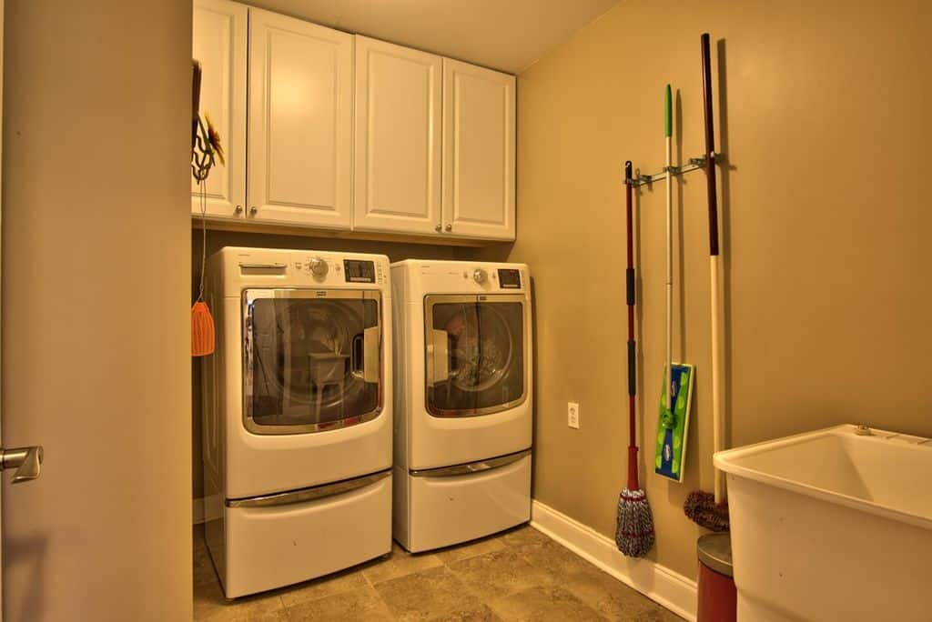 Traditional laundry room with tile flooring and built-in storage along with mop holder on wall.