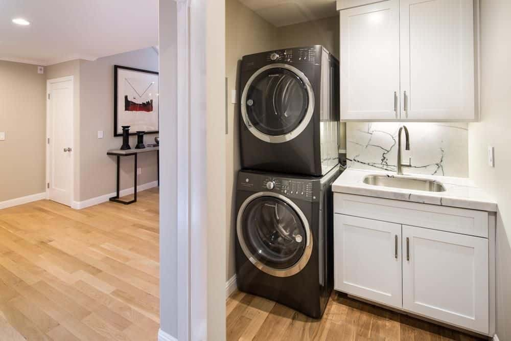 The stylish black washer and dryer look perfect together with the white cabinetry and white counter with marble countertop.