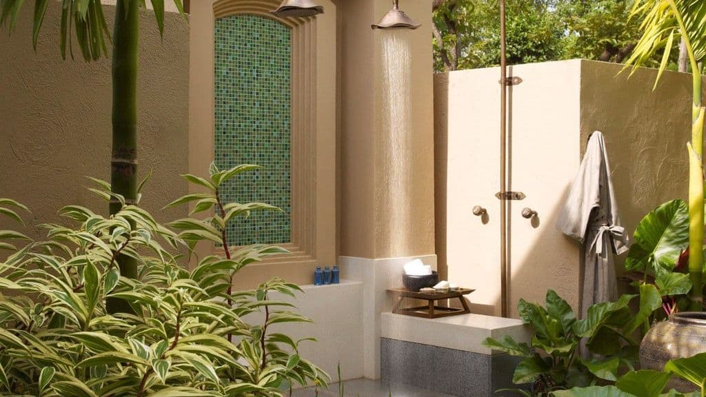This classy outdoor bathroom boasts a stunning shower space surrounded by beautiful greens and mature <a class=
