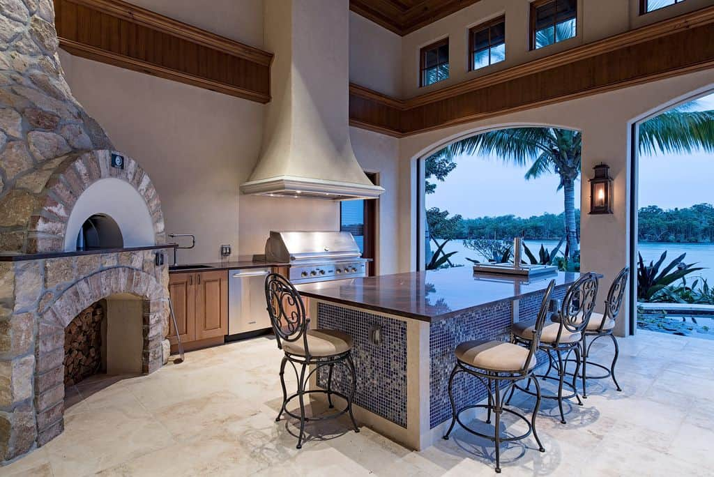 Large outdoor kitchen with a lovely center island and a fireplace. The ceiling looks absolutely perfect with this outdoor kitchen style.
