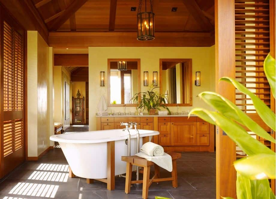 Yellow primary bathroom boasts a dual sink vanity and a freestanding bathtub lighted by a caged chandelier that hung from the wooden ceiling.