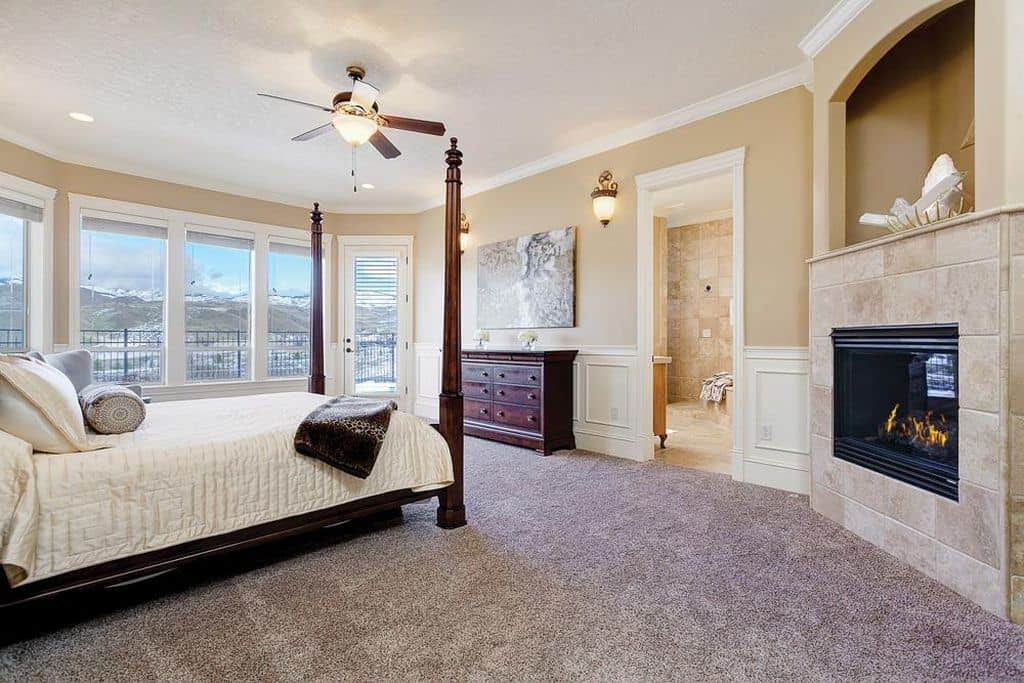 Carpeted bedroom in beige with constrasting shades from a fireplace, dark wooden bed frames and a small storage dresser. The room also features an access door to the balcony and multiple fixed windows for natural lighting.