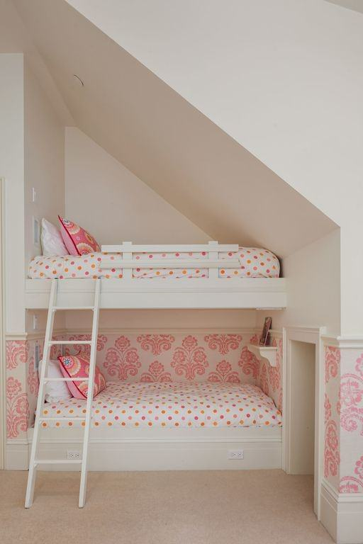 Small girl's bedroom with two-story bed and carpet flooring, surrounded by white walls with pink accent.