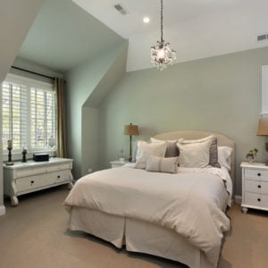 Guest bedroom with vaulted ceiling, green walls, white ceiling and pendant lights.