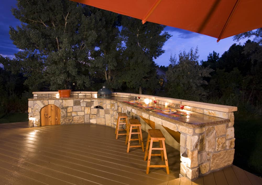 Large outdoor kitchen on a deck at night.