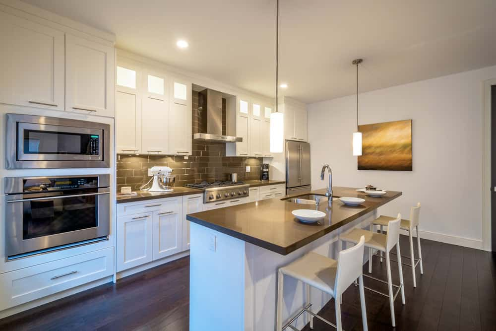 A single wall kitchen featuring hardwood floors and white walls. It also features a center island with space for a breakfast bar lighted by pendant lights.