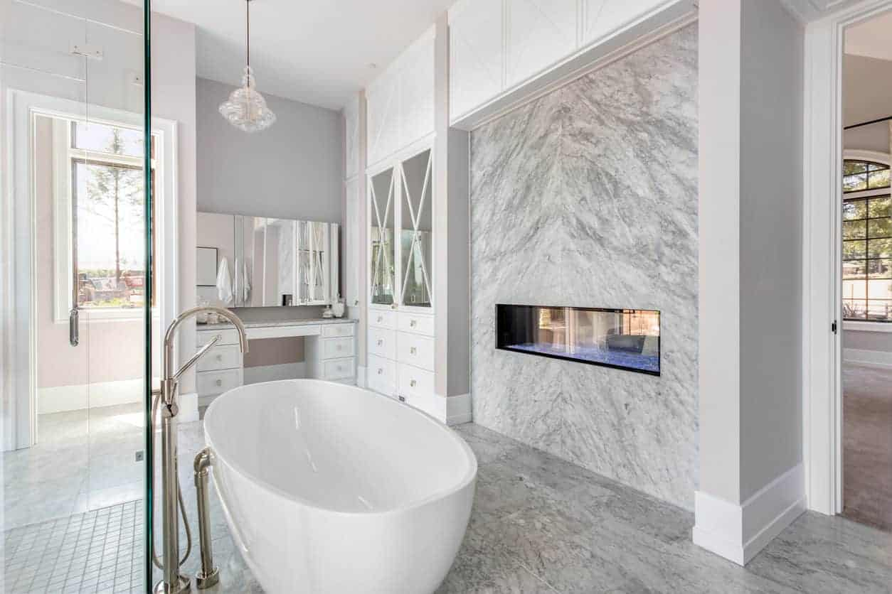 Contemporary gray and white primary bathroom with floating gas fireplace next to the freestanding tub.