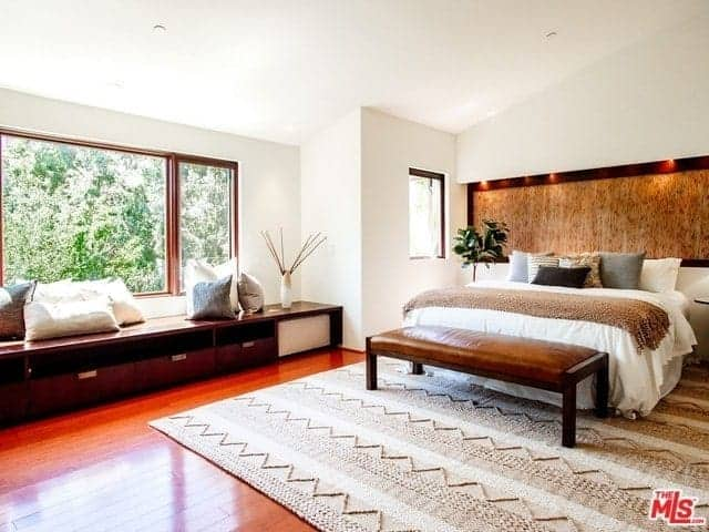 The bright white shed ceiling and walls are all contrasted by the dark hardwood flooring topped with a light brown woven area rug underneath the white bed that has a small cushioned bench at the foot. This matches with the wooden bench by the window.