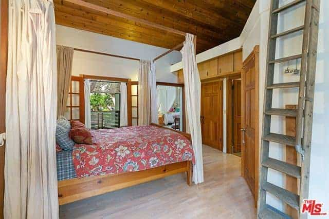 The wooden four-poster bed of this Asian-style bedroom blends with the wooden ceiling and the wooden elements that are embedded into the white walls like the cabinets, doors and frames. These are adorned by the charming floral red sheets of the bed.