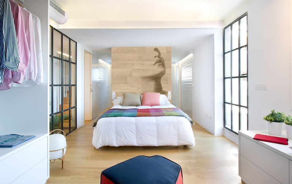 The bright white bed sheet is adorned with colorful pillows and a bed scarf as well as a large wooden panel by the head of the bed that has a large mural of a woman. This wooden panel matches the hardwood flooring that is brightened by the windows.