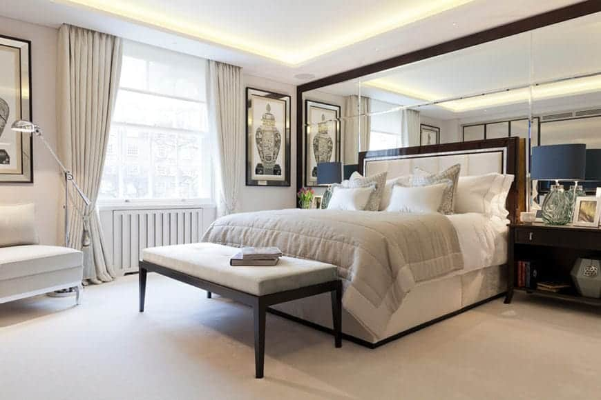 The white traditional bed has a cushioned headboard with a wooden border that matches the frame of the large mirror that dominates the wall behind the bed. This gives a sense of the room being bigger than it actually is. It also reflects the lights of the white tray ceiling.