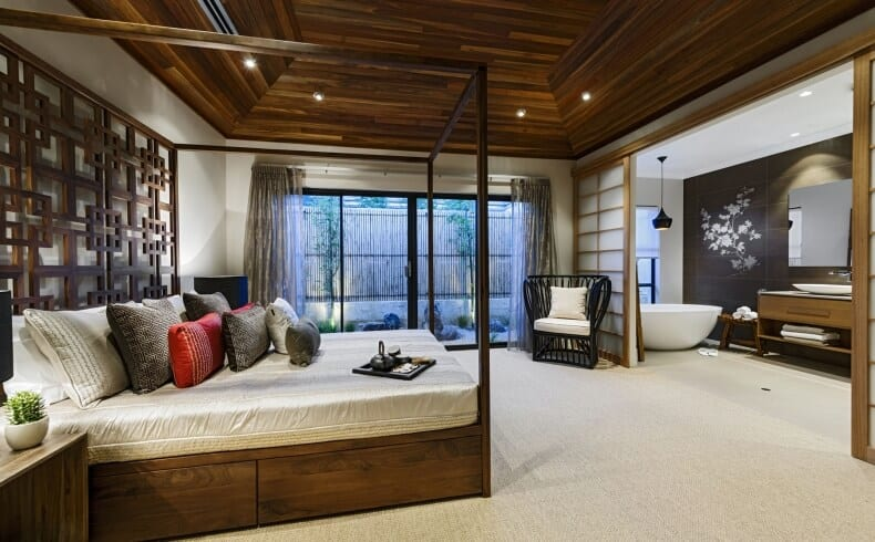 This Asian-style primary bedroom has a wooden four-poster bed with an off-white sheet that matches the carpeted flooring. The wooden hue of the bed matches with the wooden cove ceiling with recessed lights. By the foot of the bed is a large wall opening to the bathroom through sliding wooden doors.