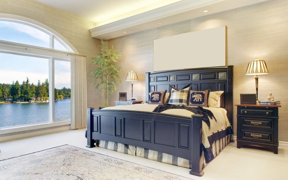 The elegant black wooden sleigh bed has beige sheets that match the beige wallpaper that contrasts the black bedside drawers. These are all illuminated by the large arched glass window on the side of the bed that features a lakeside scenery.