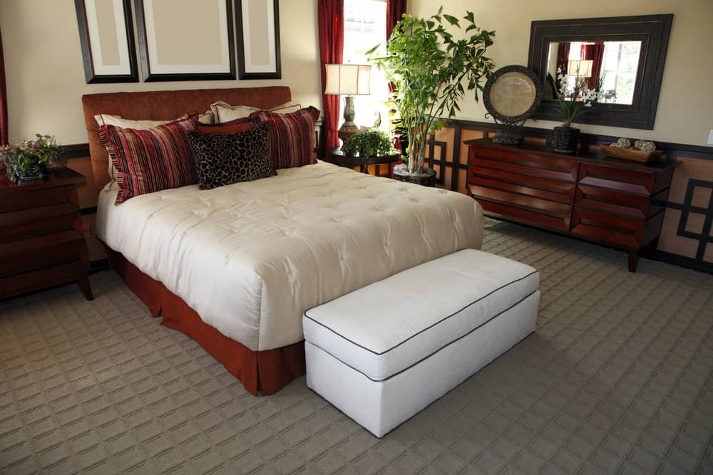 The light beige upper walls of this room is paired with a wainscoting that has a distinct Asian-style design to it. This complements the gray patterned carpeting of the floor that makes the red cushions of the bed stand out as well as the white cushioned bench at the foot of the bed.