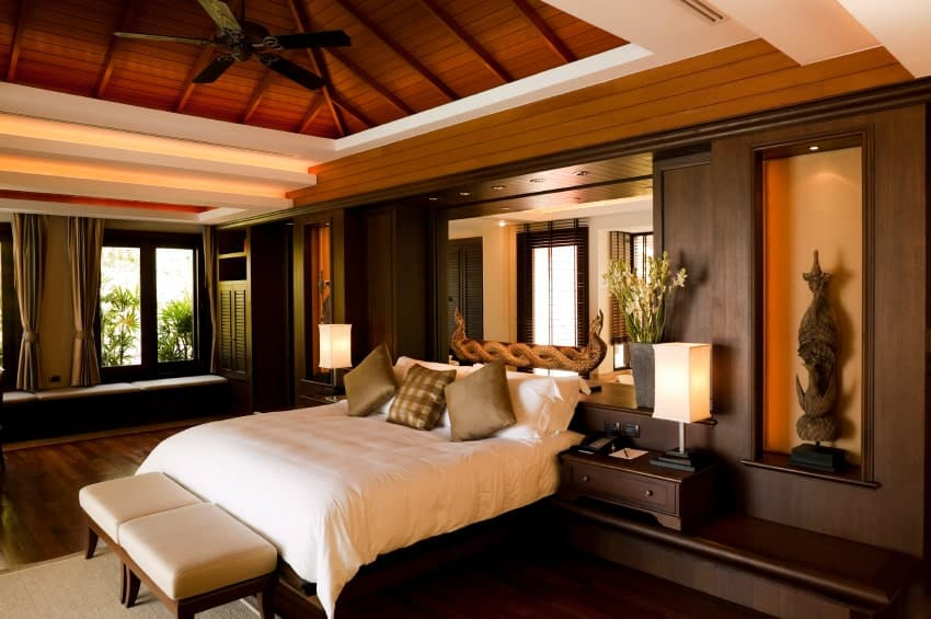 Asian primary bedroom with pitched beam ceiling, a ceiling fan, wall mirror against the headboard, built-in shelves.