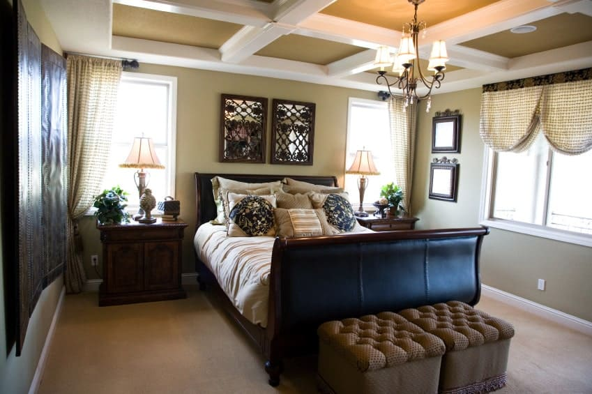 The dark wooden sleigh bed stand out against the beige carpeted flooring and light gray walls that extend to the ceiling accented with white coffers and a small chandelier that casts out warm yellow lights. This is augmented by the natural lights of the windows.