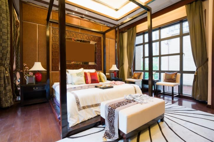 The large four-poster bed dominates this Asian-style primary bedroom that has a bright white tray ceiling trimmed with gold. This pairs well with the finish of the wall behind the headboard that has a slight golden hue due to the accent of the yellow lights.
