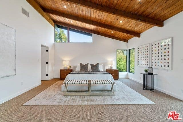 This is a spacious primary bedroom that has a minimalist feel to its Asian-style sensibility. The high wooden shed ceiling that has exposed wooden beams match with the bedside drawers of the large bed that is on a light gray area rug over the beige carpeted flooring.