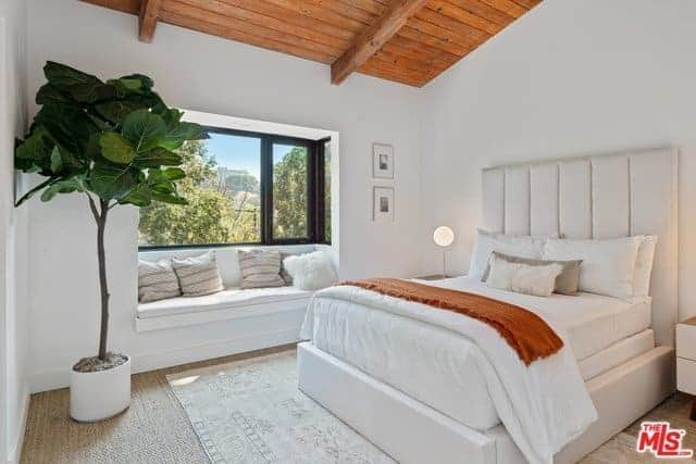 The potted plant at the corner beside the built-in sitting area under the window stands out against the white walls and the white bed with a large cushioned headboard. These are complemented by the beige carpeted flooring as well as the wooden shed ceiling.