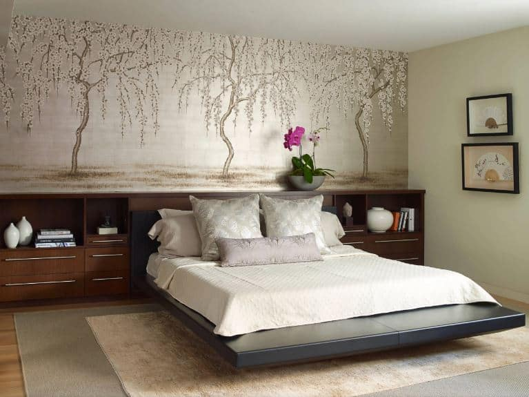 This bright Asian-style bedroom has a dark gray floating platform bed that is paired with a long wooden cabinet with built-in shelves and drawers to serve as bedside furniture. Above this is three large images of a flowering trees with an off-white background.