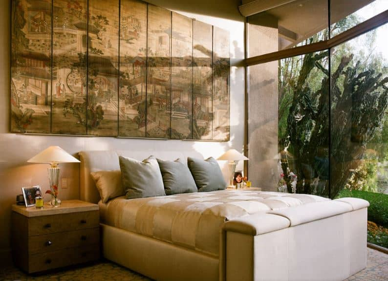 The beige cushioned sleigh bed is paired with beige cushions and beige pillows and topped with a large classic Asian painting mounted on the wall behind the head of the bed. This works well with the tall glass window that features the green landscaping.