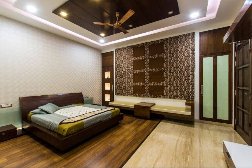 The white tray ceiling has a wooden middle tray that has a dark brown hue. This supports a golden modern ceiling fan and it also matches the wooden platform bed and the large wall filled with patterns on the side of the bed that has a built-in bench.