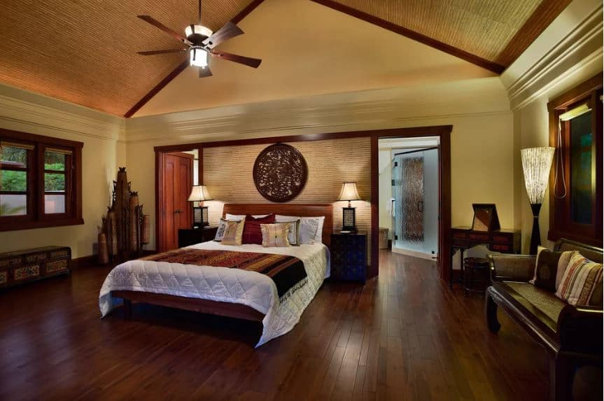 The spacious hardwood flooring of this Asian-style bedroom matches with the wooden traditional bed that is adorned with a large round carving that is mounted over the headboard of the bed that is flanked by table lamps that cast yellow lights.