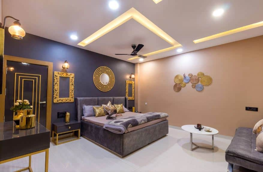 This Asian-style bedroom has a distinct Indian vibe on its golden patterns and accents that stand out against the charcoal gray walls, bed, bedside tables and the couch opposite the bed that contrasts the white flooring and ceiling.