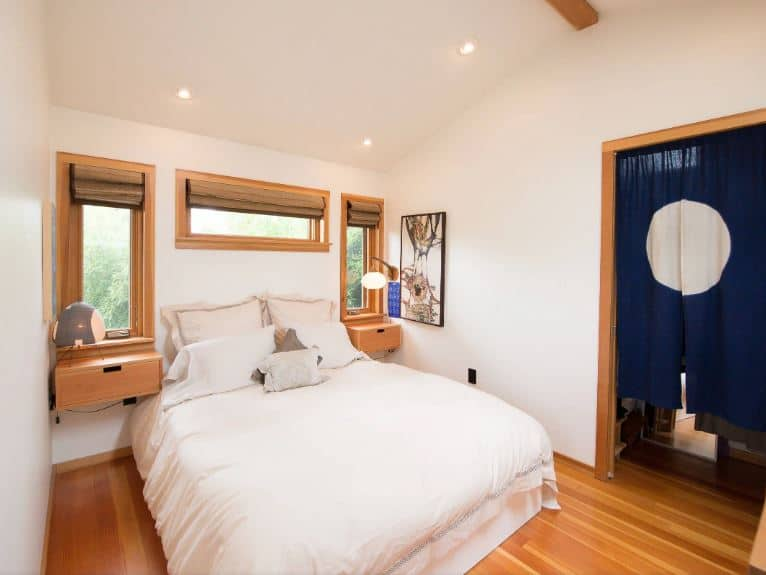 This charming bedroom has a walkway that leads to the bathroom adorned with a Japanese-style cloth curtain. Its blue hue makes it stand out against the white walls as well as the white bed and white ceiling. These are all balanced by the wooden elements like the hardwood flooring and the frames of the windows and doors.
