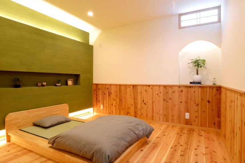 This is a simple Asian-style bedroom with a Japanese sensibility. The wooden low platform bed matches the wooden wainscoting and the hardwood flooring. These ar complemented by the green wall behind the bed as well as the ceiling and upper walls.