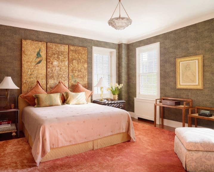 This is a charming chic Asian-style bedroom that has a salmon pink area rug covering most of the hardwood flooring. This rug complements the light pink sheets of the bed that has a beige cushioned headboard adorned with a three-part artwork mounted above.
