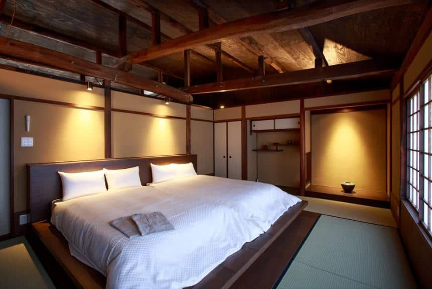 This is a Japanese-style primary bedroom with simple carpeted flooring that contrasts the low bed and its white sheets. The beige walls and alcoves are lit with warm yellow lights coming from the exposed wooden beams of the ceiling.