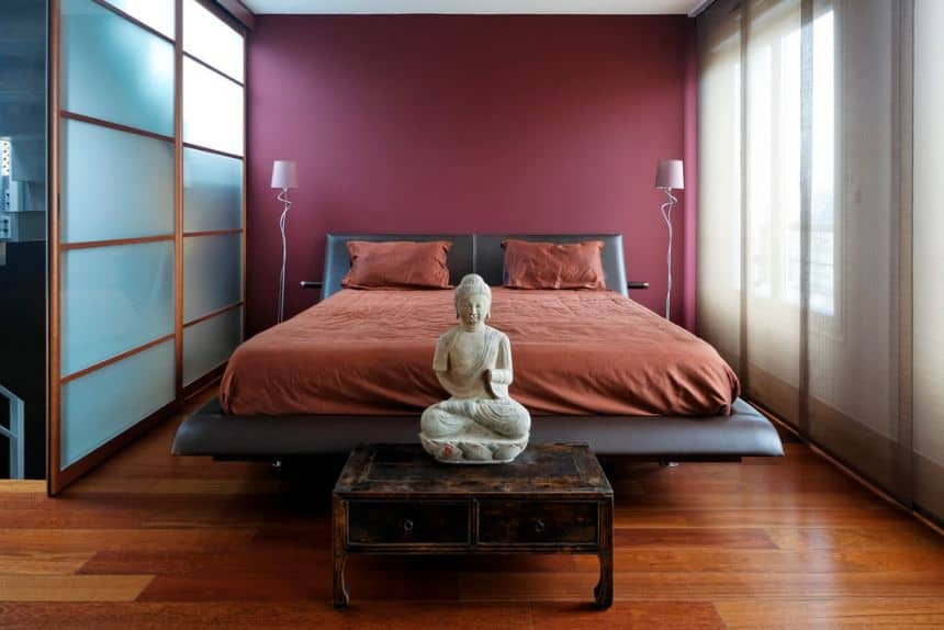 The frame of this bed looks like a giant lounge chair that has a black leather cushion. It is complemented by the red sheets of the bed and the red pillows as well as the maroon wall behind it. At the foot of the bed is a small wooden drawer that bears a statuette of Buddha.