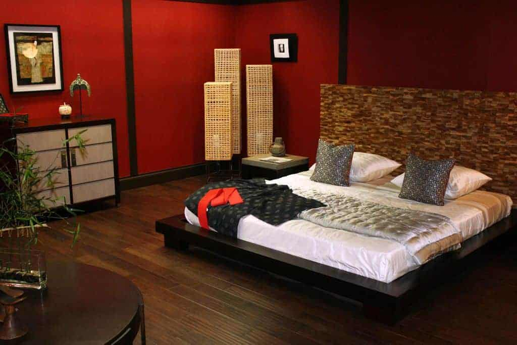 The low dark wooden bed frame is contrasted by the white sheets of the bed and complemented by the dark brown wooden headboard that stand out against the dark red walls. On the corner beside the bed is a trio of standing lamps that also stand out due to their woven wicker covers.