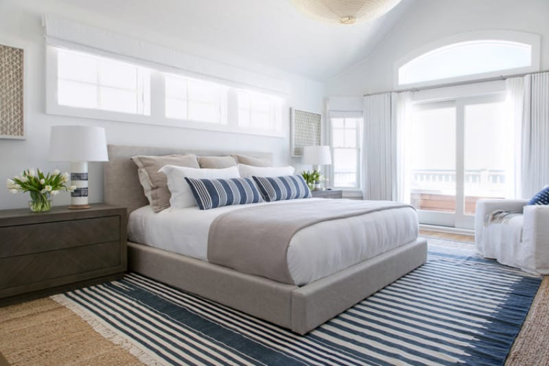 A focused look at this beach style primary bedroom with a large modern cozy bed set on top of the area rug covering the room's hardwood flooring. There are large bedside tables topped by a couple of classy table lamps.