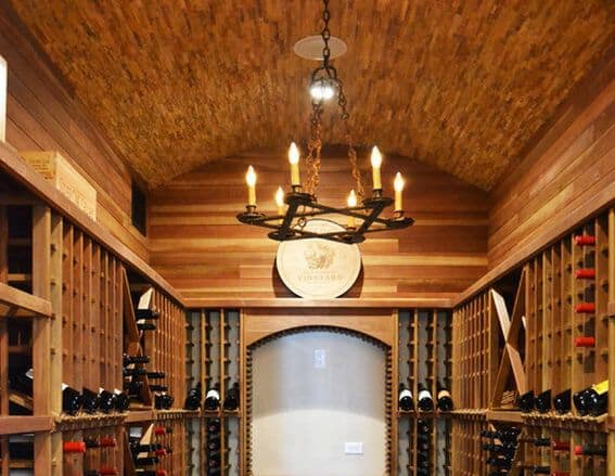 An all-wood wine cellar with a barrel-vaulted ceiling and lighted by a rustic candle chandelier.