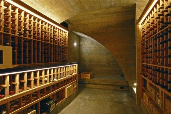A barrel-vaulted wine cellar with a narrow counter on the left and a curved nook area for storing boxes.