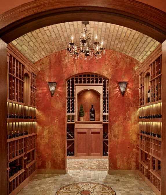 A bold red with touches of gold wine room features a mosaic floor that matches the brick ceiling. It is lighted by a fancy candle chandelier and sconces on each side of the archway between the two rooms.