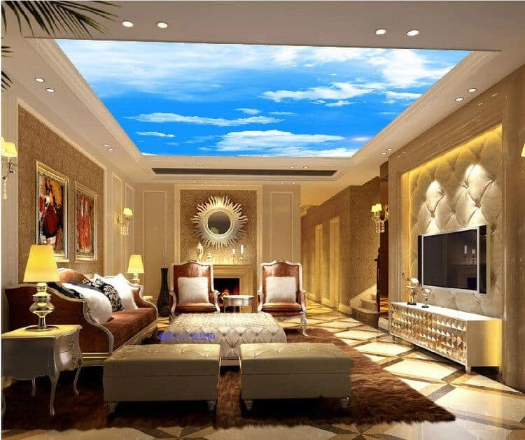 A lovely bright-blue sky photo ceiling in an elegant, luxurious living room with button tufting, gold patterned wall paper, and a sun-shaped mirror.