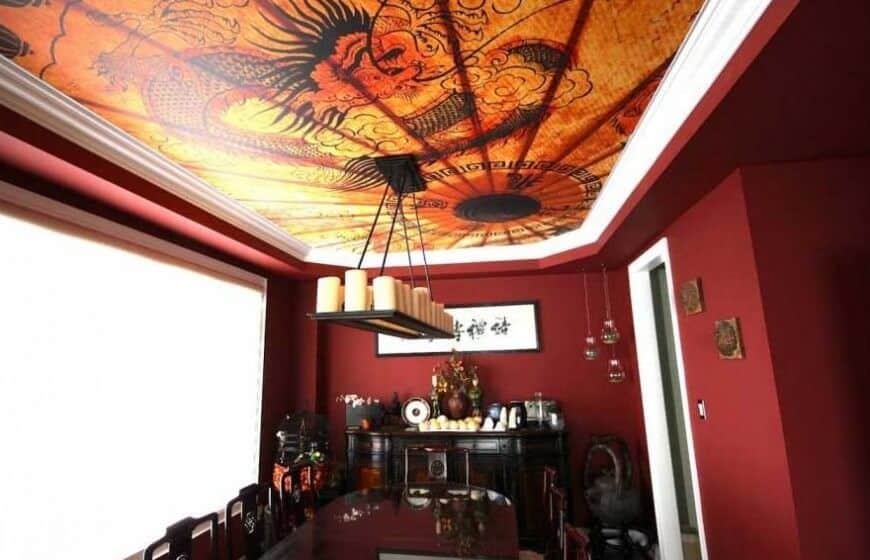This beautiful red room embraces Chinese design with a custom photo ceiling featuring a dragon. The light fixture has a series of pillar candles above the table.