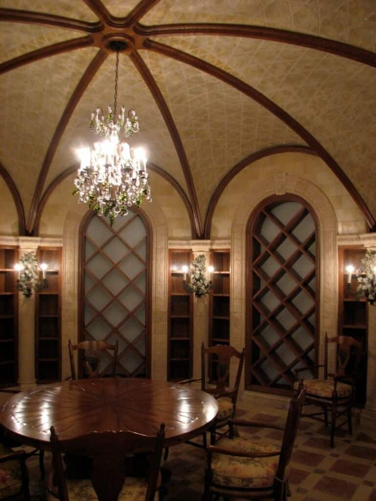 A circular wine cellar surrounded by empty racks and illuminated by lovely leafy sconces that match the crystal chandelier. At the center of the room is a large round table with floral cushioned chairs.