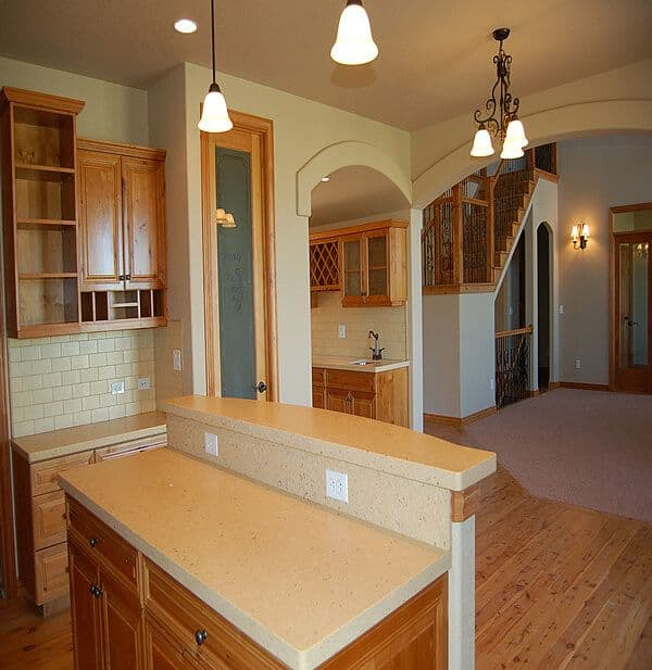 Contemporary kitchen with small island. Dual archways leading into another small kitchen area and open foyer.