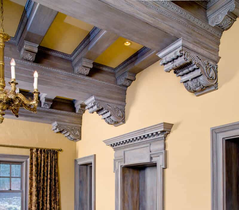The carved details on the dusky brown coffered ceilings match the details on the top of the doors. The chandelier is also ornately detailed.