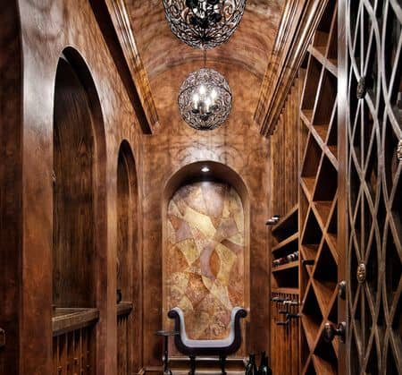 An elegant wine cellar with features an inset on the back wall along with a small settee. Matching wrought iron orb chandeliers hang from the barrel vaulted ceiling.