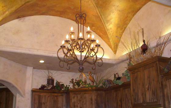 This gilded groin vault rises above the beige walls and natural wood cabinetry of this kitchen.