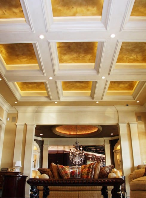 Textured and backlit panels are crossed by white beams and molding. Through the archway is a grand room with a dome ceiling.