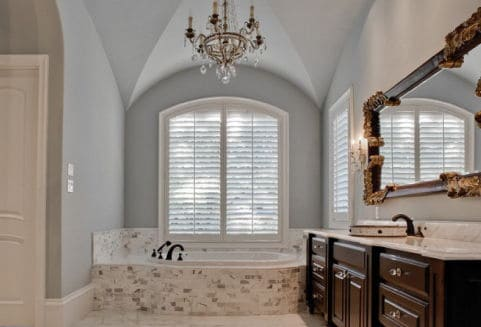 A soaring groin vault in the bathroom, paired with the cool gray paint bring a feeling of airy relaxation which complements the more ornate mirror and chandelier.