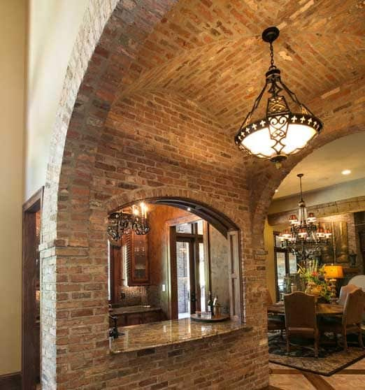 A groin vault in brick with a cut-out window to the kitchen ensures that this dining room and kitchen feel open and inviting.
