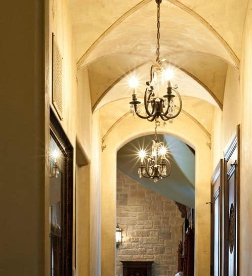 Another hallway with multiple groin vaults with light fixtures hanging from the center.