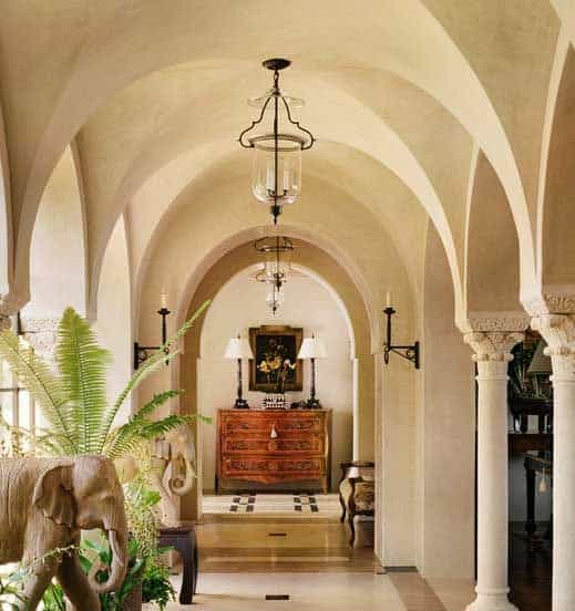 Another lovely white hallway with columns and light fixtures hanging from the center of each groin vault.